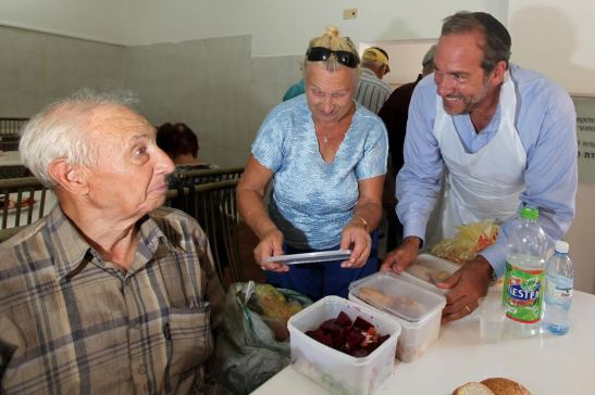 Rabbi Yechiel Eckstein serves food to needy people at the Mana Hama Soup Kitchen in Ashdod, Israel. RYE wearing a blue shirt and white apron packs up plastic containers of food next to a woman with blonde hair and sunglasses wearing a blue shirt and an elderly man in a brown plaid shirt